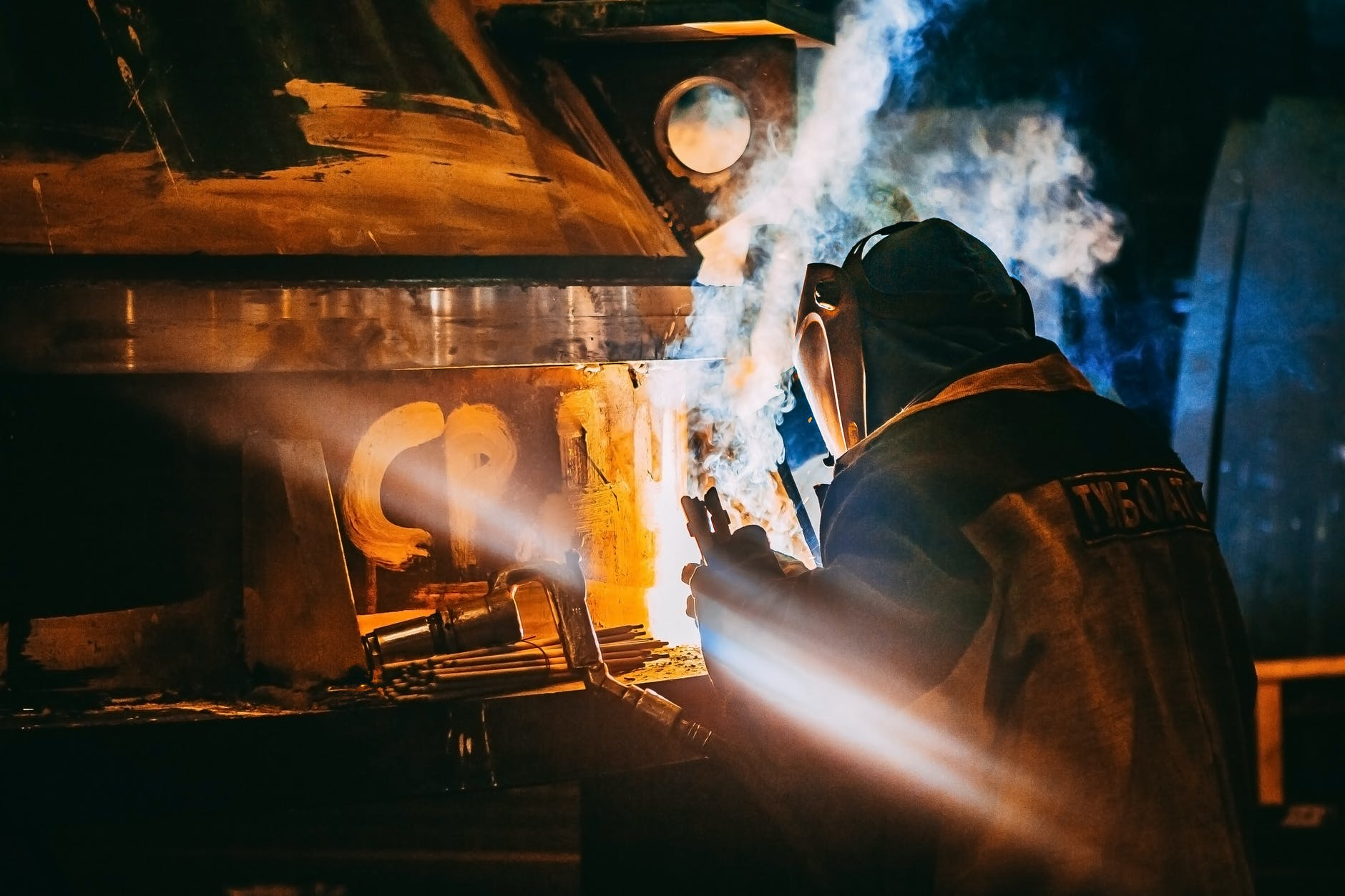 person wearing gray jacket and welding helmet